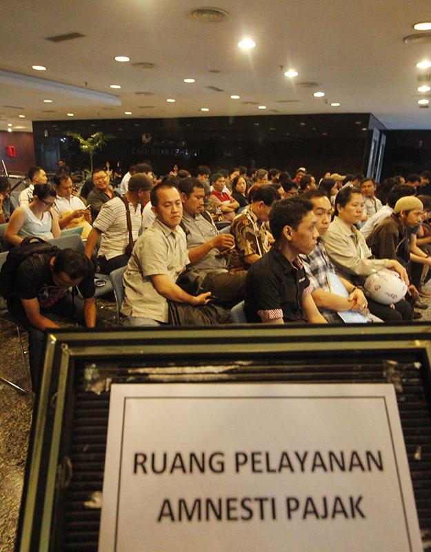 Sejumlah warga menunggu panggilan untuk ikut dalam program Tax Amnesty di Kantor Dirjen Pajak, Jl. Jenderal Gatot Subroto, Jakarta, Sabtu (24/9). Program Tax Amnesty digelar selama 9 bulan sejak 18 Juli hingga 31 Maret 2017 dan terbagi atas tiga periode masing-masing selama tiga bulan dengan jumlah tebusan amnesti Pajak per 23 September Rp 38,3 Triliun, Deklarasi dan Repatriasi Rp.1.604 Triliun. ANTARA FOTO/Reno Esnir/ama/16.