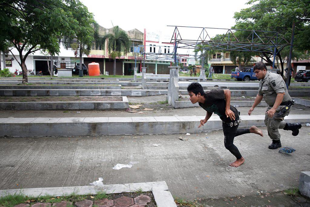 Petugas Satpol PP dan Wilayatul Hisbah mengejar anak punk yang berupaya melarikan diri saat razia penyakit masyarakat (pekat) di Terminal Keudah, Banda Aceh, Aceh, Kamis (3/11). Razia yang dilaksanakan secara persuasif dengan melibatkan personil Satpol PP, WH, aparat TNI/Polri dan pegawai Dinsos berhasil menjaring puluhan pengemis, gelandangan serta anak punk yang akan ditempatkan di rumah singgah untuk pembinaan. ANTARA FOTO/Irwansyah Putra/foc/16.